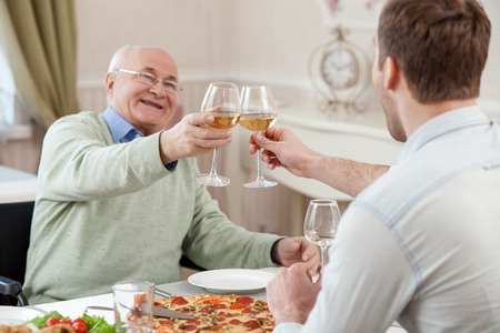 Photo for Pretty old man and his son are drinking wine at home. They are clicking glasses and smiling. The men are sitting at the table with joy - Royalty Free Image