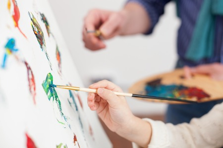 Photo for Close up of arms of grandfather and granddaughter painting together - Royalty Free Image
