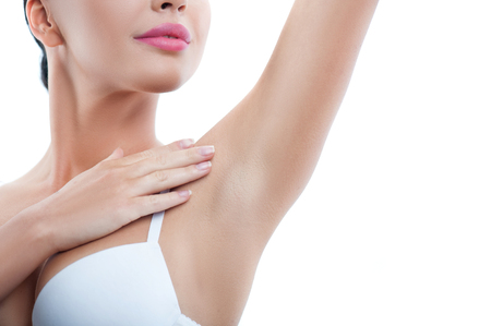 Foto de Cheerful girl is touching her smooth armpit with satisfaction. She is standing and raising her arm up. Isolated and copy space in right side - Imagen libre de derechos