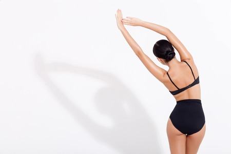 Foto de Attractive slim girl is standing in tight underwear and stretching her body. She is raising arms arm and bending sideways. Focus on her back. Isolated and copy space in left side - Imagen libre de derechos