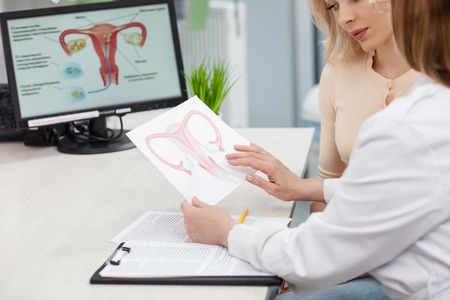 Photo pour Experienced female gynecologist is explaining to a woman the concepts of her disease. She is holding and showing a picture of uterus. Young lady is looking at it seriously - image libre de droit