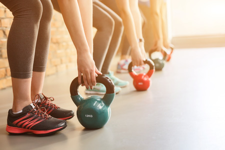 Photo for Close up of female arms lifting kettlebell in gym. Group of women are standing in row - Royalty Free Image