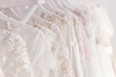 Photo pour Close up of white wedding dresses hanging on rack - image libre de droit