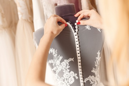 Foto de Close up of arms of designer buttoning wedding dress on mannequin - Imagen libre de derechos