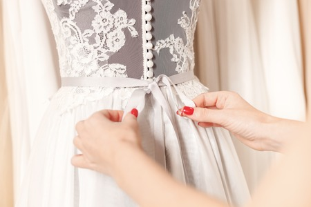 Photo pour Close up of female hands adjusting bow on back of wedding clothing - image libre de droit