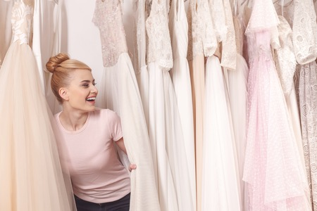 Photo pour Pretty young woman is hiding between wedding dresses in boutique. She is laughing with happiness - image libre de droit