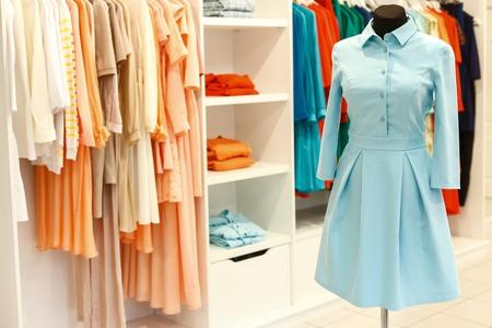 Photo pour Fashionable designer dress on mannequin near clothes on hangers in boutique - image libre de droit