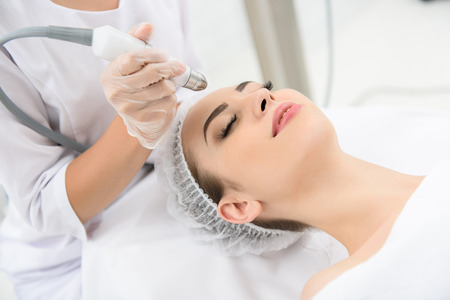Photo pour Young woman is getting a laser skin treatment in healthy beauty salon. She is lying on table with relaxation. Her eyes are closed - image libre de droit