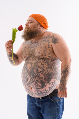 Foto de Happy fat man is holding tulip and smelling it with pleasure. He is standing and smiling. Isolated - Imagen libre de derechos