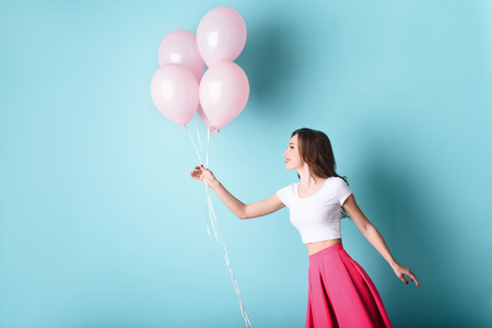 Photo for Carefree woman playing with pink balloons. Isolated and copy space on left side - Royalty Free Image