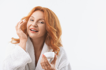 Photo pour Joyful middle-aged woman is applying cream on her face. She is looking at camera with happiness and smiling. Woman is standing in white bathrobe. Isolated and copy space in right side - image libre de droit