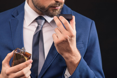 Photo for Self-confident young businessman is enjoying smell of masculine perfume. He is standing and holding bottle. Isolated - Royalty Free Image