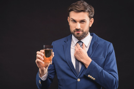 Foto de Attractive young businessman is presenting bottle of masculine perfume. She is adjusting tie and looking at camera with confidence. Man is standing in suit. Isolated - Imagen libre de derechos
