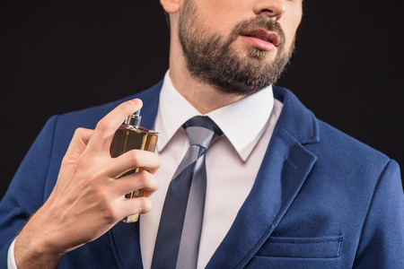 Photo for Sexy young man is perfuming himself with masculine cologne. She is standing and posing in suit with confidence. Isolated - Royalty Free Image