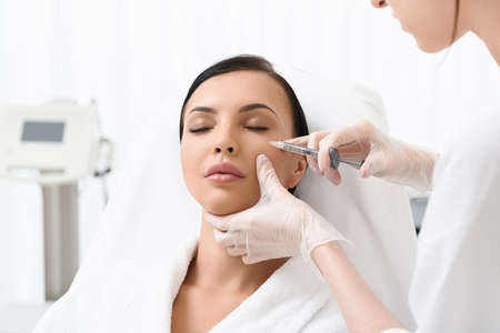 Photo pour Beautiful young woman is caring of her skin at beautician office. She is sitting and getting botox injection. Her eyes are closed with tranquility - image libre de droit