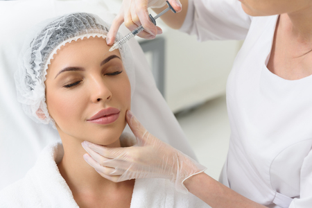 Photo pour Serene young woman is getting botox injection into her forehead. She is sitting in doctor office and relaxing - image libre de droit