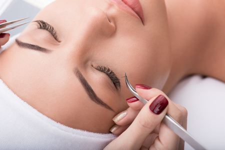 Photo for Close up of female face. Beautician building up long artificial eyelashes for young woman - Royalty Free Image