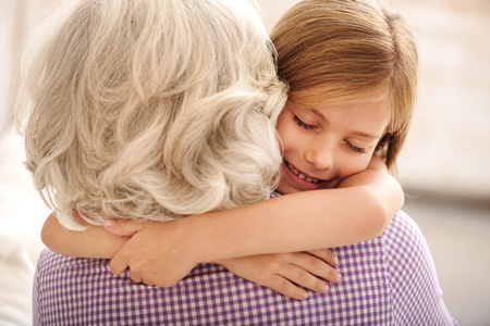 Photo pour Affectionate granddaughter and grandmother are hugging. Girl is smiling with closed eyes - image libre de droit