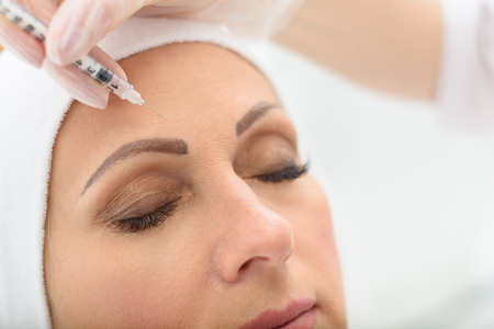 Photo pour Close up of senior woman face getting botox injection at clinic. Her eyes are closed with serenity - image libre de droit