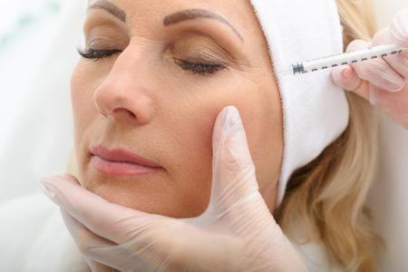 Photo pour Close up of mature female face getting rejuvenation injection by beautician. Woman closed eyes calmly - image libre de droit