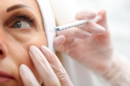 Photo pour Close up of doctor hands injecting hyaluronic acid into female wrinkles eye area - image libre de droit