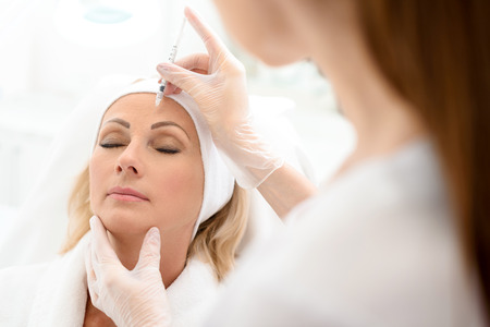 Photo pour Skillful beautician is injecting botox into female forehead. Senior woman sitting with tranquility - image libre de droit