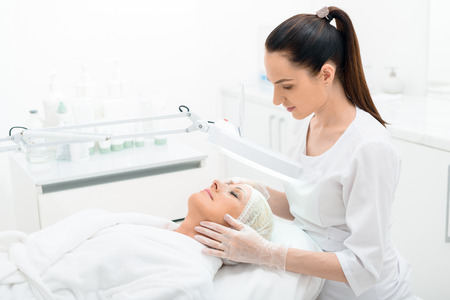 Photo for Professional beautician is examining female facial skin through lamp with concentration - Royalty Free Image