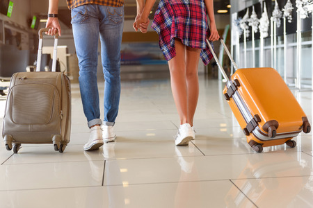 Foto de Close up of legs of young man and woman walking at airport with suitcases. They are holding hands - Imagen libre de derechos