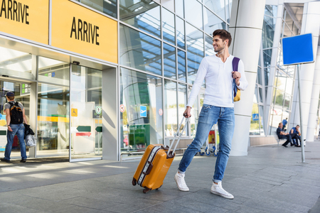 Photo for Happy young man arrived from trip. He is walking from airport with luggage and smiling. Guy is looking back and smiling - Royalty Free Image