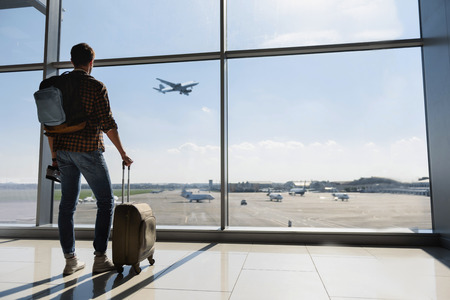 Foto de Young man is standing near window at the airport and watching plane before departure. He is standing and carrying luggage. Focus on his back - Imagen libre de derechos