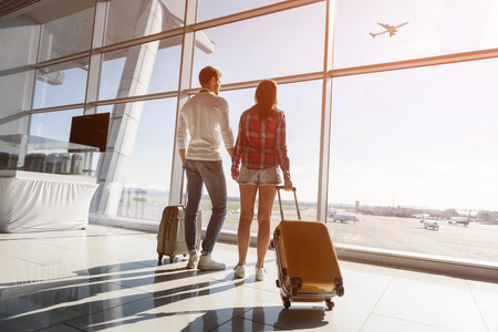 Photo pour Cute loving couple is watching flight and sunset at airport. They are standing near window and carrying suitcases - image libre de droit