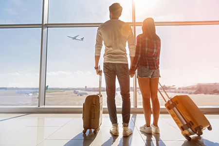 Photo pour Inspired young loving couple is looking at flying plain in sky. They are standing near window at airport and holding hands - image libre de droit