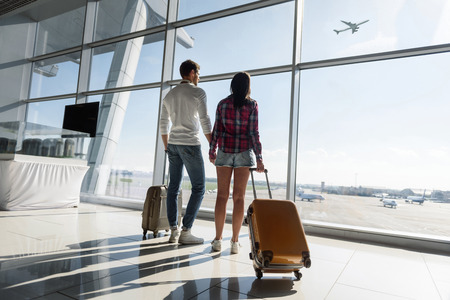 Photo pour Young man and woman are looking through window at airport dreamingly. They are carrying luggage and holding hands - image libre de droit