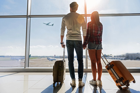 Foto de We are ready for new future. Young man and woman are watching flight at airport. They are standing and carrying luggage - Imagen libre de derechos