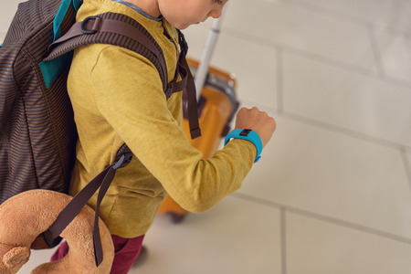 Foto per Almost time for my flight. Top view shot of little boy looking at smart watch, being at airport and standing near suitcase - Immagine Royalty Free