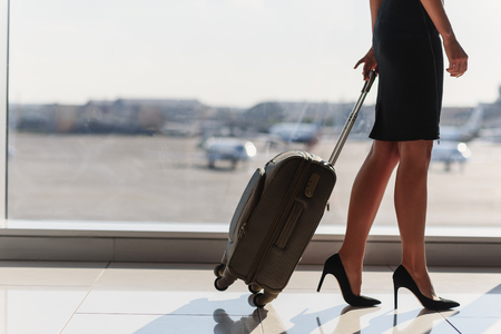 Photo pour Close up of legs of elegant woman going on business trip. She is standing in airport and carrying suitcase - image libre de droit