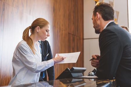 Photo pour Assisting client with pleasure. Young female receptionist helping mature man to check in at hotel while searching for his name in list - image libre de droit