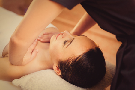 Photo pour Serene girl is enjoying massage at spa. Masseuse is standing and pampering her breast - image libre de droit