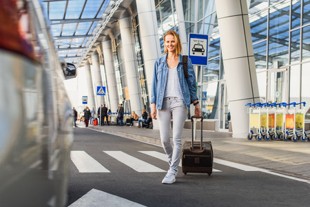 Photo for Cheerful young woman is going to taxi from the airport. She is carrying suitcase and smiling - Royalty Free Image