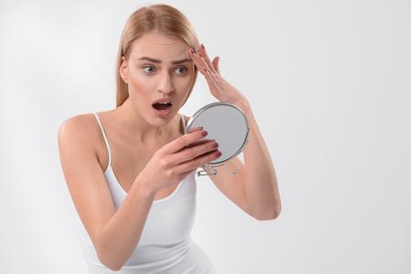 Photo pour Surprised woman observing her facial skin - image libre de droit
