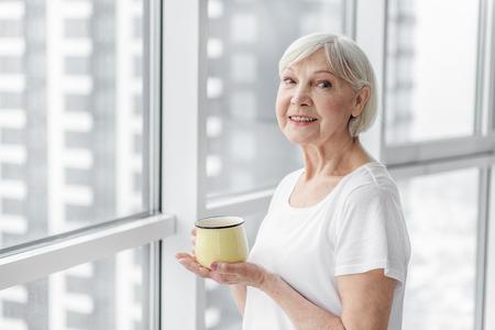 Photo pour Happy senior lady enjoying hot drink - image libre de droit