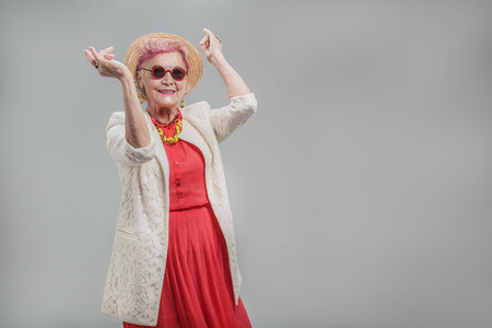 Photo for Happy beautiful senior lady wearing sunglasses and hat - Royalty Free Image