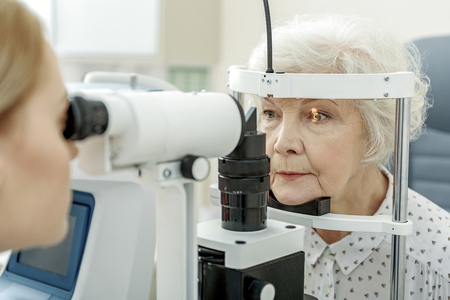 Photo for Young female ophthalmologist using apparatus - Royalty Free Image