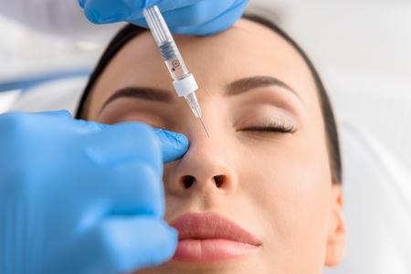 Photo pour Serene female receiving collagen in nose - image libre de droit