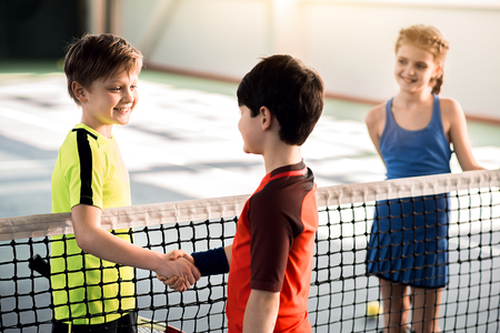 Photo for Cheerful boys shaking hands before playing tennis - Royalty Free Image