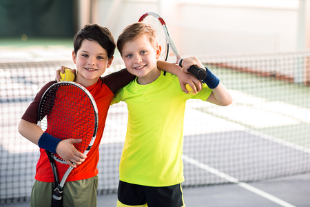 Photo for Happy children entertaining on tennis court - Royalty Free Image