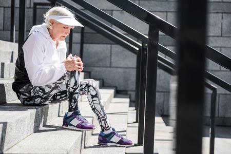 Photo pour Depressing aged woman having rest on stone stadium ladder - image libre de droit