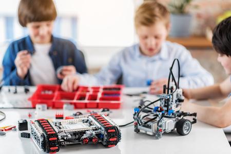 Foto de Ready made robots at table afore boys - Imagen libre de derechos