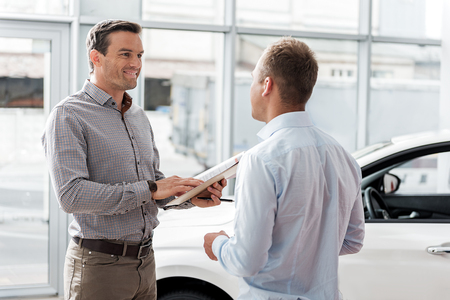 Foto per Outgoing man telling with worker in car dealership - Immagine Royalty Free