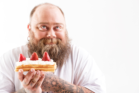 Photo pour Happy thick guy enjoying tasty cake - image libre de droit